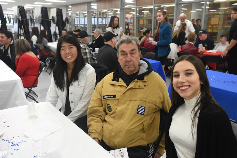 Philip Schubitz, center, Vietnam-era veteran who served with the U.S. Army from 1968 to 1970, pauses for a photo with student Lauren Oda (left) and Jessica Pavliukovecas, during the Elk Grove High School Veterans Day ceremony, Nov. 9, 2018.