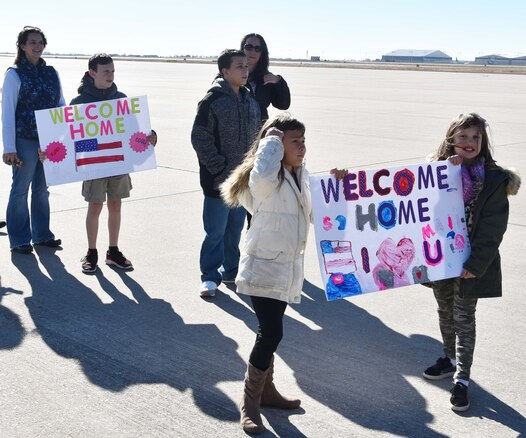 Family members of 931st Air Refueling Wing members hold homemade signs as they await the return of their loved ones Nov. 15, 2018, McConnell Air Force Base, Kan. More than 35 members of the 931 ARW returned from a deployment to Turkey.