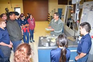 Tech. Sgt. James Gomez, 433rd Aircraft Maintenance Squadron machinist and welder, describes how a computer numerical control machine is used to create replacement parts for the C-5M Super Galaxy to Rowlett High School Air Force Junior Reserve Officer's Training Corps cadets at Joint Base San Antonio-Lackland, Texas Nov. 9, 2018.