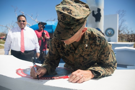 Col. Robert Brodie, commanding officer of the 31st Marine Expeditionary Unit, signs the 31st MEU logo during a Veteran's Day ceremony on Tinian, Commonwealth of the Northern Mariana Islands, Nov. 12, 2018. The Mayor's Office here commissioned the work in honor of the Marines and Sailors of the 31st MEU who have been working to since Oct. 29 to assist local and CNMI officials during relief efforts in the wake of Super Typhoon Yutu, which struck here Oct. 25 as the second strongest storm to ever hit U.S. soil. Marines and Sailors with the 31st MEU and CLB-31 arrived on Tinian Oct. 29-31 to lead relief efforts on Tinian in response to Yutu as part of Task Force-West. TF-W is leading the Department of Defense's efforts to assist CNMI's local and civil authorities provide critical assistance for citizens devastated by Yutu. The 31st MEU, the Marine Corps' only continuously forward-deployed MEU, provides a flexible force ready to perform a wide-range of military operations across the Indo-Pacific region. (U.S. Marine Corps photo by Lance Cpl. Hannah Hall/Released)