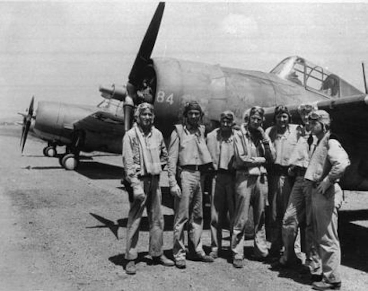 World War II aircrew stands in front of an airplane.