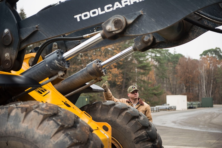 U.S. Air Force Tech. Sgt. Brock Butschke, 435th Construction and Training Squadron pavements and equipment contingency instructor, gives signals to a front loader operator during a civil engineer training event on Ramstein Air Base, Germany, Nov. 15, 2018. The 786th Civil Engineer Squadron reached out to the 435th CTS to assist with its Prime Base Engineer Emergency Force training. (U.S. Air Force photo by Senior Airman Joshua Magbanua)