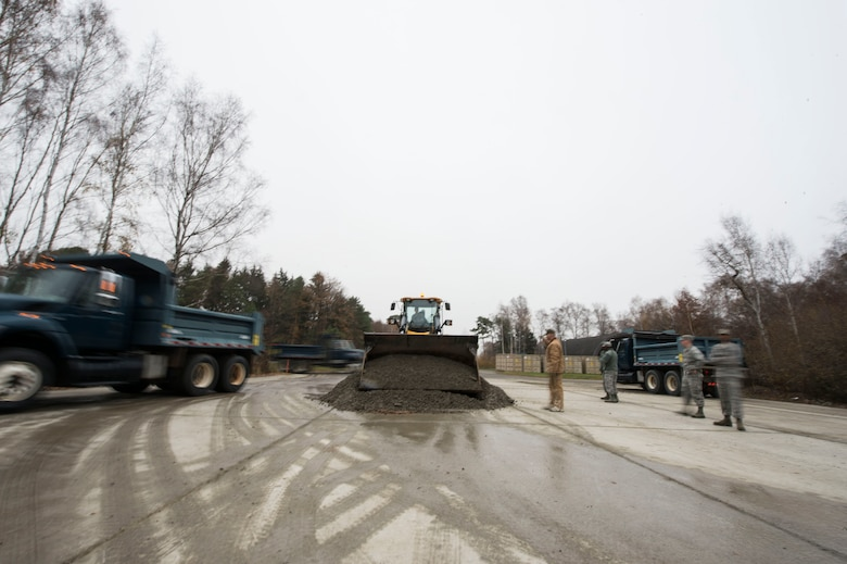 U.S. Airmen assigned to the 786th Civil Engineer Squadron move a gravel pile as part of a training event on Ramstein Air Base, Germany, Nov. 15, 2018. Leaders at the 786th CES bolstered their squadron's Prime Base Engineer Emergency Force readiness with assistance from instructors assigned to the 435th Construction and Training Squadron. (U.S. Air Force photo by Senior Airman Joshua Magbanua)