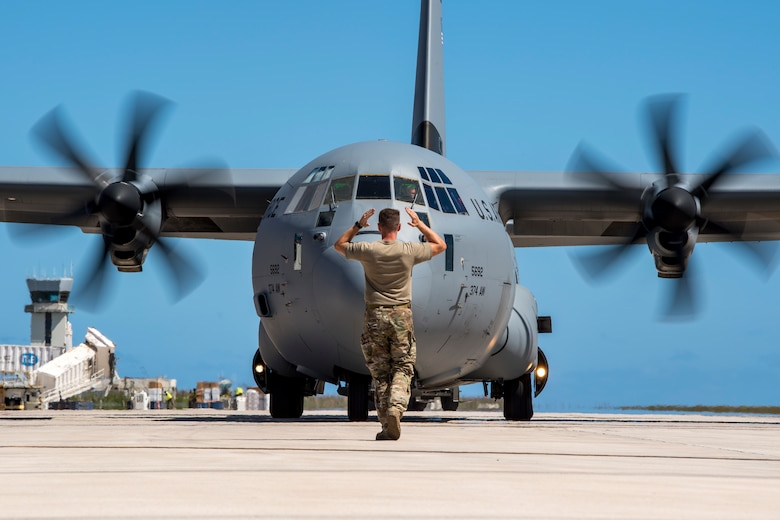 An airman marshals in a C-130J Super Hercules