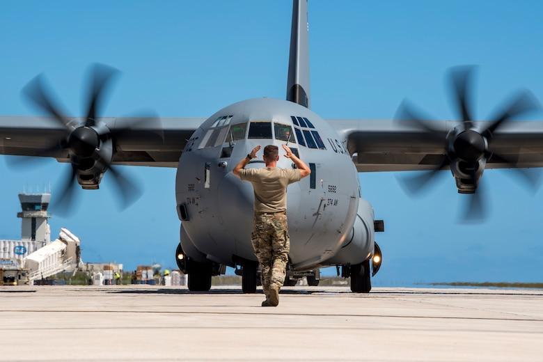 An airman marshals in a C-130J Super Hercules