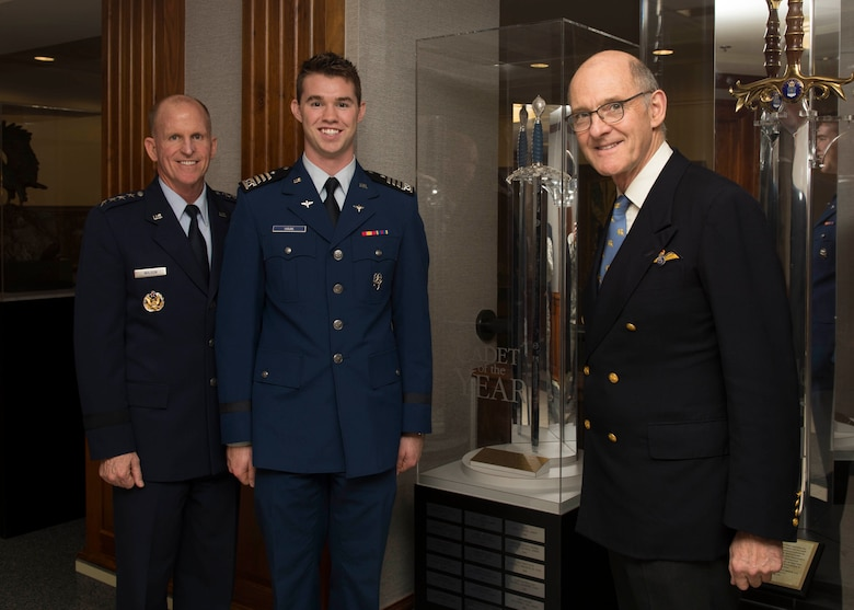 Air Force Vice Chief of Staff Gen. Stephen V. Wilson, Cadet 2nd Class Kyle Haak and Dr. The Hon. Gilbert Greenall, Commodore of the Royal Air Squadron, pose for a photo in front of the Millennium Sword at the Pentagon, Arlington, Va., Nov. 6, 2018. Haak was honored as the British Air Squadron's 2018 Cadet of the Year. Recipients of the award receive the Millennium Sword, which is kept on permanent display in the Pentagon. (U.S. Air Force photo by Staff Sgt. Victoria H. Taylor)
