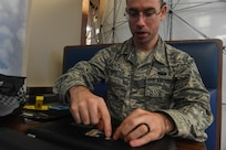 U.S. Air Force Staff Sgt. Matthew Baxter, Air Combat Command Communication Support Squadron global command and control systems administrator, takes apart a personal computer before recycling it during America Recycles Day at Joint Base Langley-Eustis, Virginia, Nov. 15, 2018. The 633rd CES held a recycling event at the Base Exchange to collect grocery bags, electronics and plastics. (U.S. Air Force photo by Senior Airman Derek Seifert)