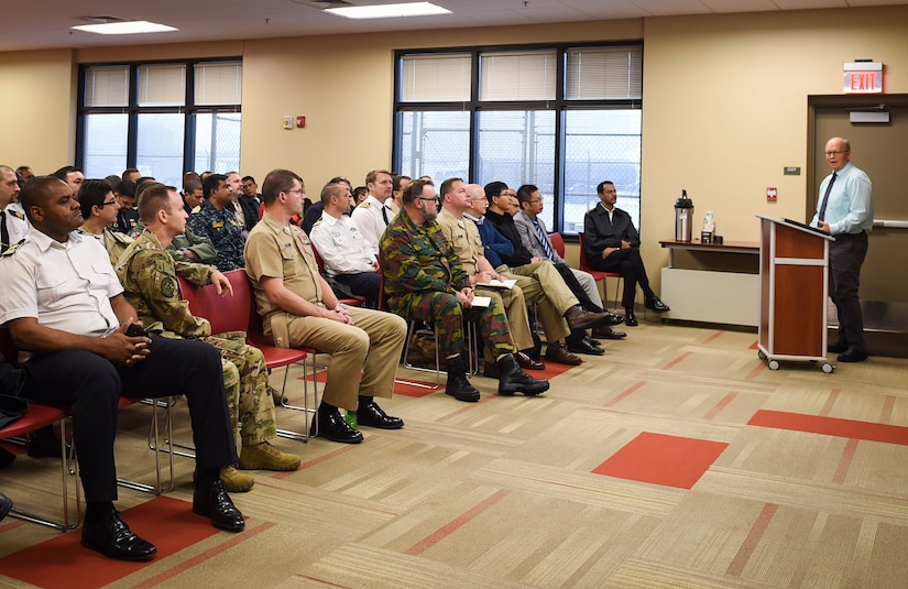 A group of Naval War College students, comprised of 56 foreign and joint military officers, listen to a mission briefing during a Nov. 13, 2018, visit to Joint Base Charleston, S.C.