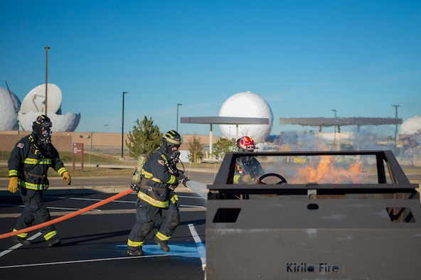 Buckley Fire Department firefighters extinguish a simulated vehicle fire during the 2018 Buckley Spouse and Family Day event Nov. 13, 2018, at Buckley Air Force Base, Colo. The fire simulation gave insight of the BFD mission capabilities. (U.S. Air Force photo by Airman 1st Class Holden S. Faul)