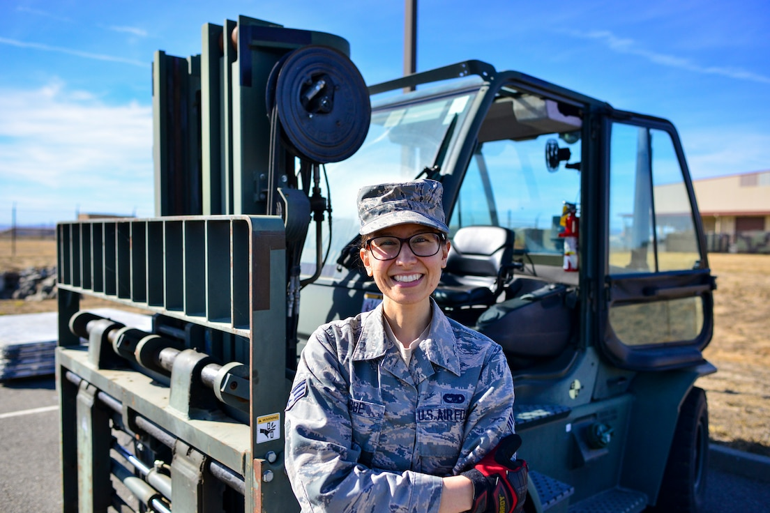 Senior Airman Catherine Lubbe, 55th Aerial Port Squadron special handling representative, poses for a photo in front of a forklift Nov. 4, 2018 at Travis Air Force Base, California.