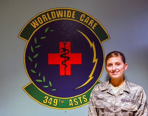 Senior Airman Nichole Savard, 349th Aeromedical Staging Squadron unit deployment manager, poses for a photo in front of her unit shield Nov. 4, 2018 at Travis Air Force Base, California.