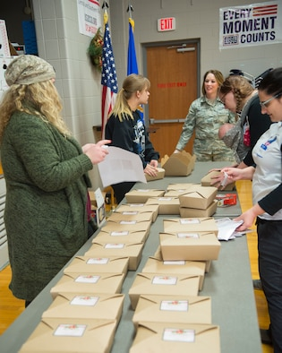 Tech. Sgt. Season Hurley, 88th Medical Support Squadron, and others pack an assortment of homemade cookies into boxes Dec. 6, 2017, at the Wright-Patterson Air Force Base USO Community Center during the annual cookie drive. Boxes of donated cookies are to be distributed this holiday season to some 1,100 unaccompanied Airmen. (U.S. Air Force photo/R.J. Oriez)