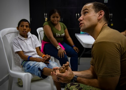 Lt. Cmdr. Matt Stepanovich, from Portsmouth, Va., examines a patient's foot at a land-based medical site.