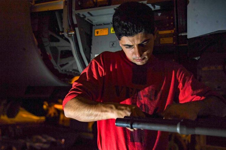 A sailor cleans a weapon.