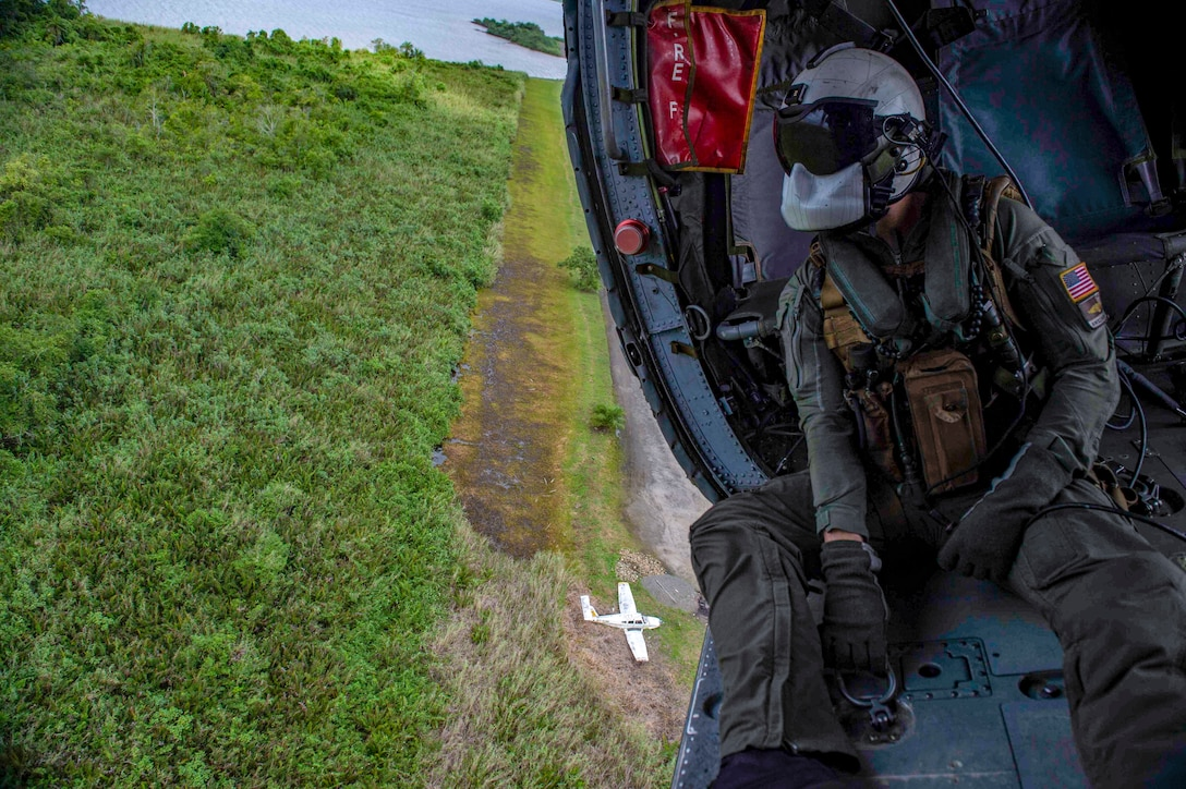 A sailor looks out from a helicopter flying over grasslands.