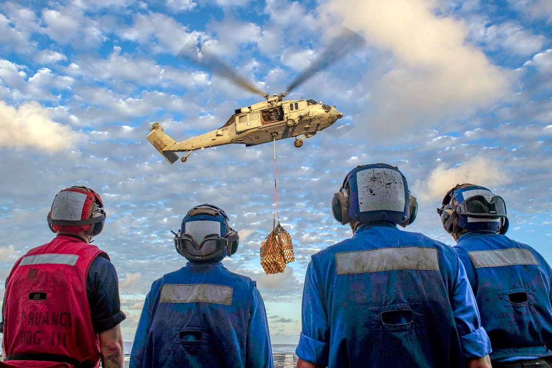 Sailors watch a helicopter carry cargo to where they will retrieve it.