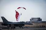 Bahrain Defense Forces parachute with the Bahrain flag above a U.S. Air Force F-16 Fighting Falcon at the Sakhir Air Base during the Bahrain International Airshow (BIAS) 2018, Bahrain, Nov. 14, 2018. BIAS is a biennial, three-day aviation and aerospace industry event that provides the U.S. military an opportunity to highlight DOD aviation's flexibility, speed and agility. (U.S. Air Force photo by Senior Airman Gracie I. Lee)