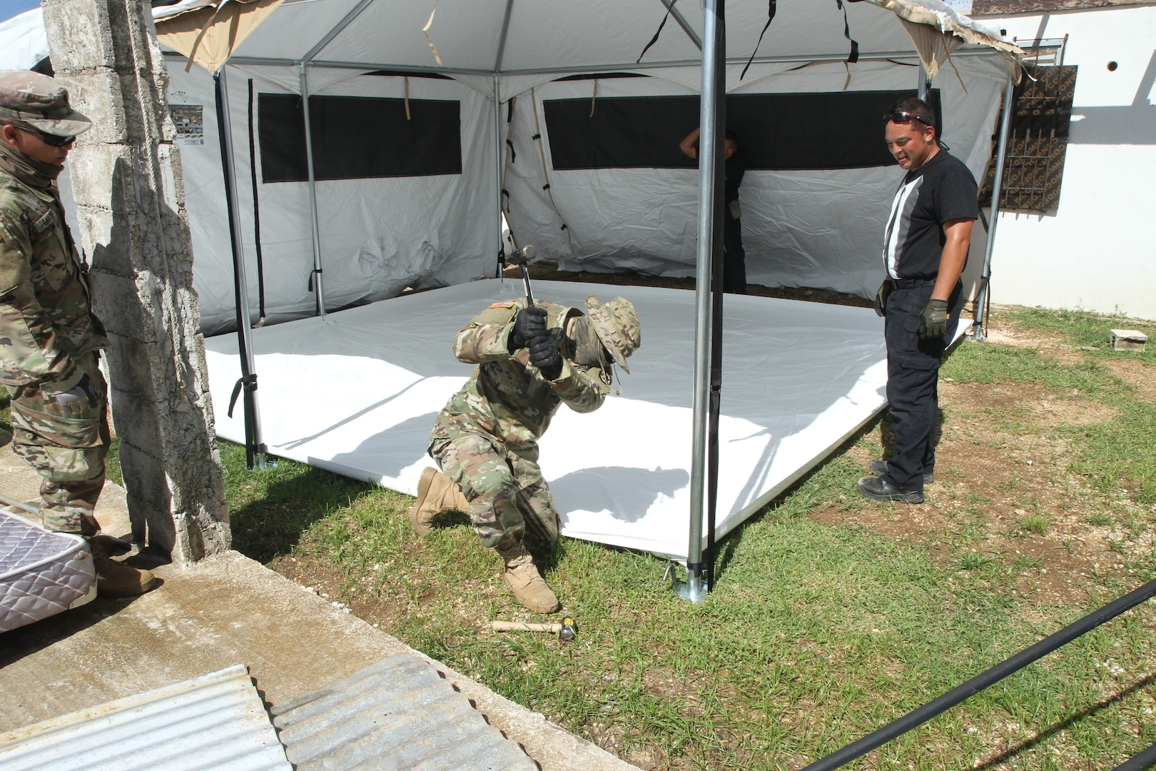 Service members build tent systems for Yutu survivors