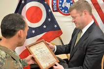 Soldier presenting Under Secretary with honorary certificate.