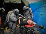 "A decontamination team of Airmen and Soldiers care for casualties in a simulated mass casualty decontamination line during the 503rd Military Police Battalion field training exercise at Camp Blanding, Fla., on Oct. 24, 2018. Army Maj. Gen. William ""Bill"" Hall participates as a mock victim of a chemical, biological, radiological and nuclear catastrophe."