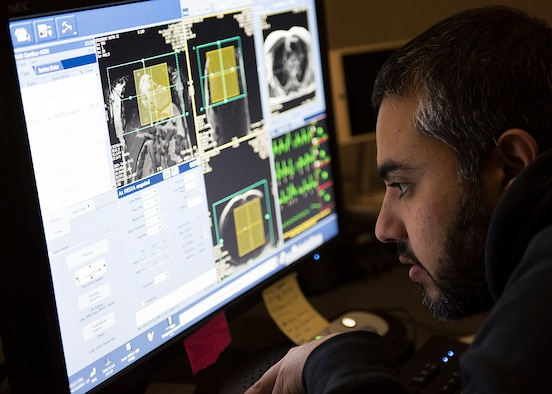 Marvin Perez, 59th Medical Wing cardiac magnetic resonance imaging technologist, observes a patient's vitals during a scan at Wilford Hall Ambulatory Surgical Center, Joint Base San Antonio-Lackland, Texas. Cardiac MRI, which takes approximately 20-45 minutes, is a non-invasive assessment of the function and structure of the heart. (U.S. Air Force photo by Staff Sgt. Kevin Iinuma)