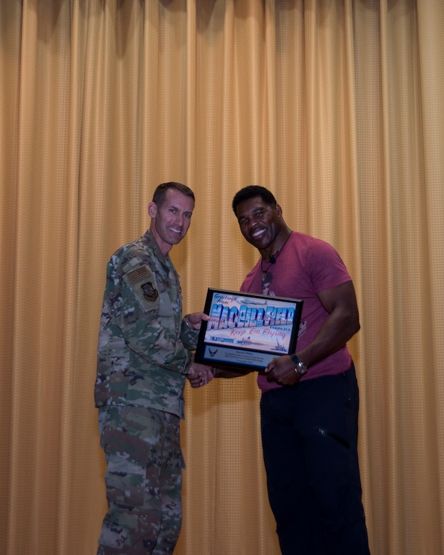 Former NFL running back Herschel Walker receives a token of appreciation from U.S. Air Force Colonel Stephen Snelson, 6th Air Mobility Wing Commander, at MacDill Air Force Base, Fla., Nov. 14, 2018.