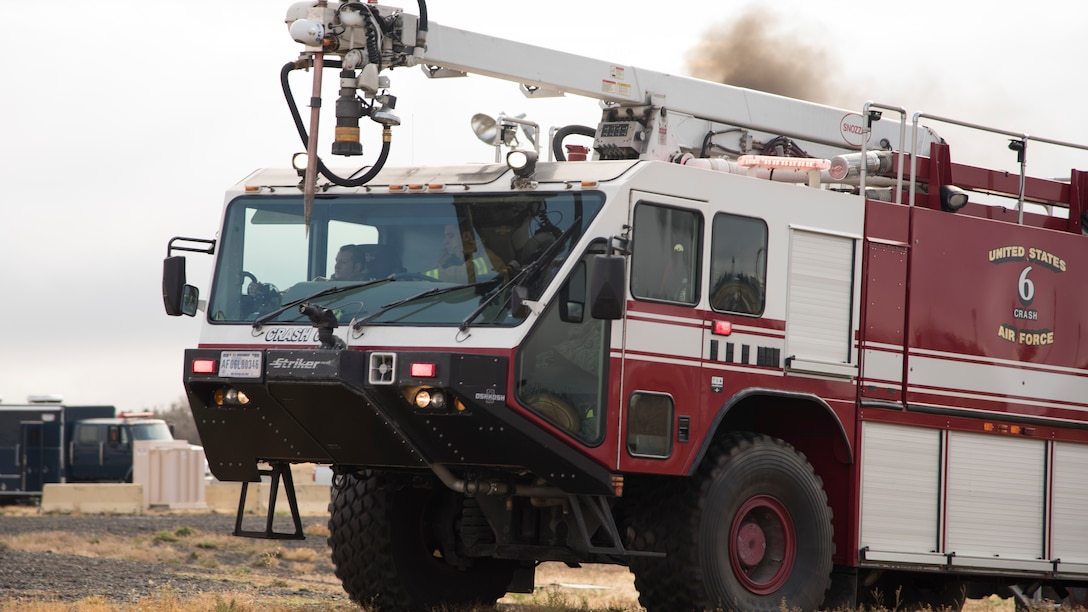 92nd Civil Engineering Squadron firefighters drive into a training area during demonstration of the bases emergency response capabilities to members of the Spokane Local Emergency Planning Committee at Fairchild Air Force Base, Washington, Nov. 7, 2018. The LEPC meets at different locations monthly to help survey local disaster response capabilities and Team Fairchild volunteered to host during the month of November as a way to demonstrate the specialized resources the base can offer to the local community. (U.S. Air Force Photo/ Senior Airman Ryan Lackey)
