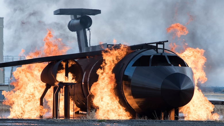 A dummy aircraft burns in the 92nd Civil Engineering Squadron Fire Department training area during a demonstration for members of the Spokane Local Emergency Planning Committee at Fairchild Air Force Base, Washington, Nov. 7, 2018. Team Fairchild firefighters use a dummy and simulate flames with safe propane gas to minimize environmental impact while maintaining readiness training efforts. (U.S. Air Force Photo/ Senior Airman Ryan Lackey)