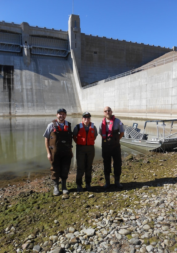 JOHN MARTIN RESERVOIR, Colo. – John Martin park rangers (l-r) Tucker Feyder, Valerie Thompson, and Christopher Gauger stand in front of the electrofishing boat at the bottom of the dam, Nov. 1, 2018. Part of the $6 million stilling basin dewatering project involves the removal of the fish from the stilling basin. Photo by Kim Falen. This was a 2018 photo drive entry.