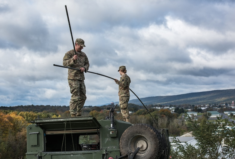 Staff Sgt. Patrick Kluyber and Staff Sgt. Chloe Rangel, both radio frequency transmission systems supervisors with the 148th Air Support Operations Squadron, Pennsylvania Air National Guard, assemble a whip antenna to mount on a Humvee.