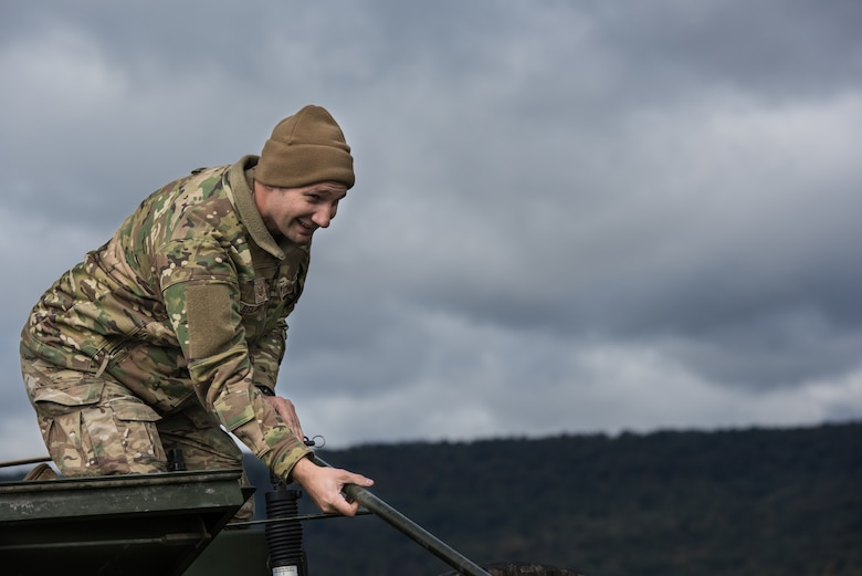 Tech. Sgt. Nathan Belanger, a radio frequency transmission systems supervisor with the 148th Air Support Operations Squadron, Pennsylvania Air National Guard, helps raise a whip antenna on a Humvee.