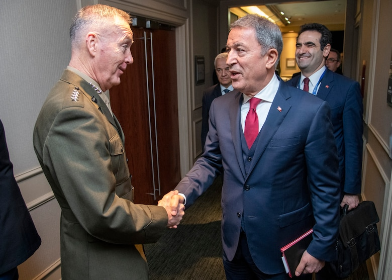Marine Corps Gen. Joe Dunford, chairman of the Joint Chiefs of Staff, greets Turkish Minister of Defense Hulusi Akar, during the Halifax International Security Forum Nov. 17, 2018.