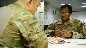 Staff Sgt. Akina Jones, 386th Expeditionary Civil Engineer Squadron force protection specialist, speaks to a fellow FP Airman Oct. 18, 2018, at an undisclosed location in Southwest Asia. Jones and her fellow force protection Airmen are comprised of individuals from more than 50 Air Force specialty codes. (U.S. Air Force photo by Staff Sgt. Christopher Stoltz)