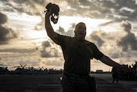Sgt. Maj. Frank Gratacos, sergeant major, Marine Aircraft Group 24, signals Marines to remove their gas masks after passing him during a gas mask run, Marine Corps Air Station, Kaneohe Bay, Nov. 16, 2018. The physical training event aimed to build unit readiness and cohesion, while also familiarizing Marines with conducting strenuous activity while wearing their gas masks.