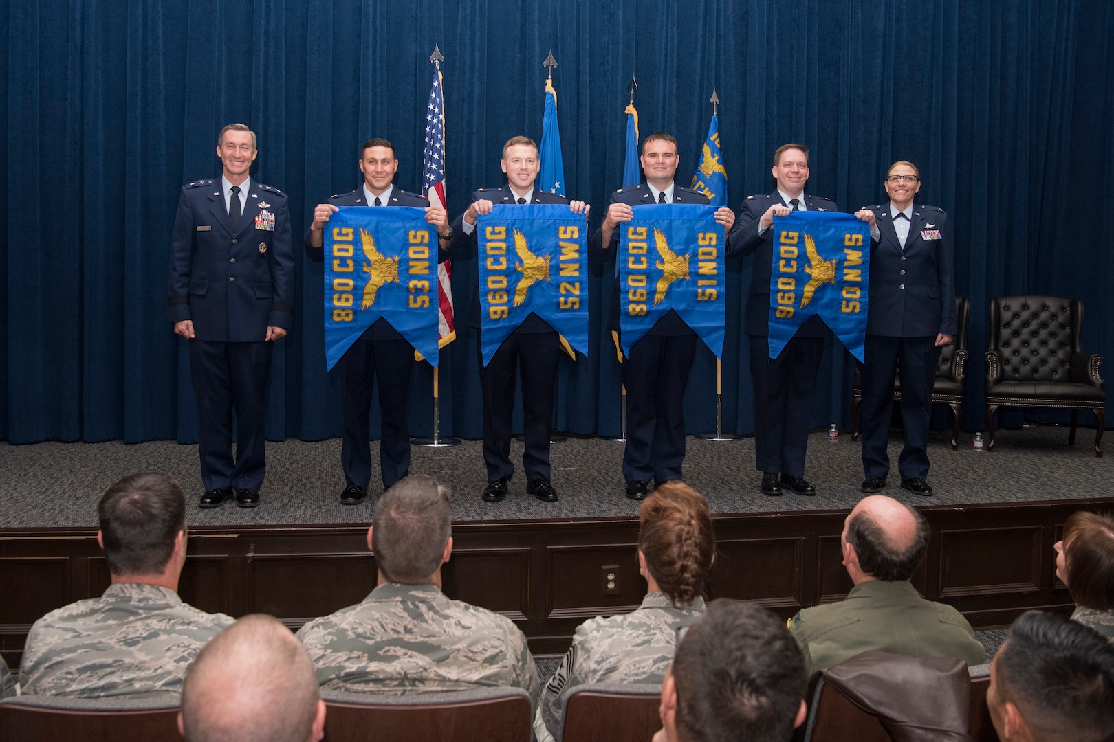 """The commanders of four of the six newly activated subordinate units of the 960th Cyberspace Wing unfurled thier unit flags and posed for a photo with Maj. Gen. Ronald """"Bruce"""" Miller, 10th Air Force commander, and Col. Lori Jones, the new 960th Cyberspace Wing commander."""