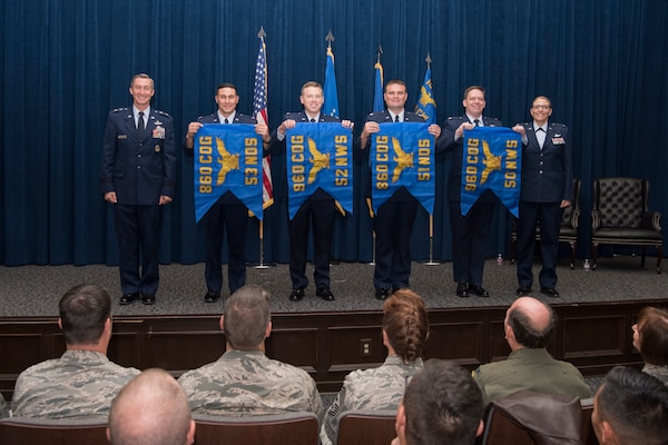 "The commanders of four of the six newly activated subordinate units of the 960th Cyberspace Wing unfurled thier unit flags and posed for a photo with Maj. Gen. Ronald ""Bruce"" Miller, 10th Air Force commander, and Col. Lori Jones, the new 960th Cyberspace Wing commander."