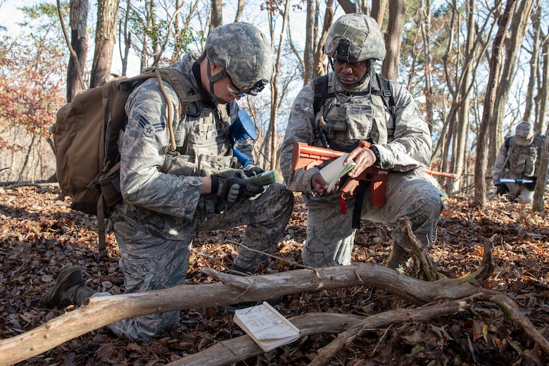 Senior Airman Mitchell Krause, 374th Security Forces Squadron patrolman, left, and Staff Sgt. Rayon McDonald 374 SFS flight chief, right, utilize a Defense Advanced GPS Receiver (DAGR) to mark coordinates in a notebook during a field training exercise at Camp Fuji, Japan, Nov. 8, 2018.
