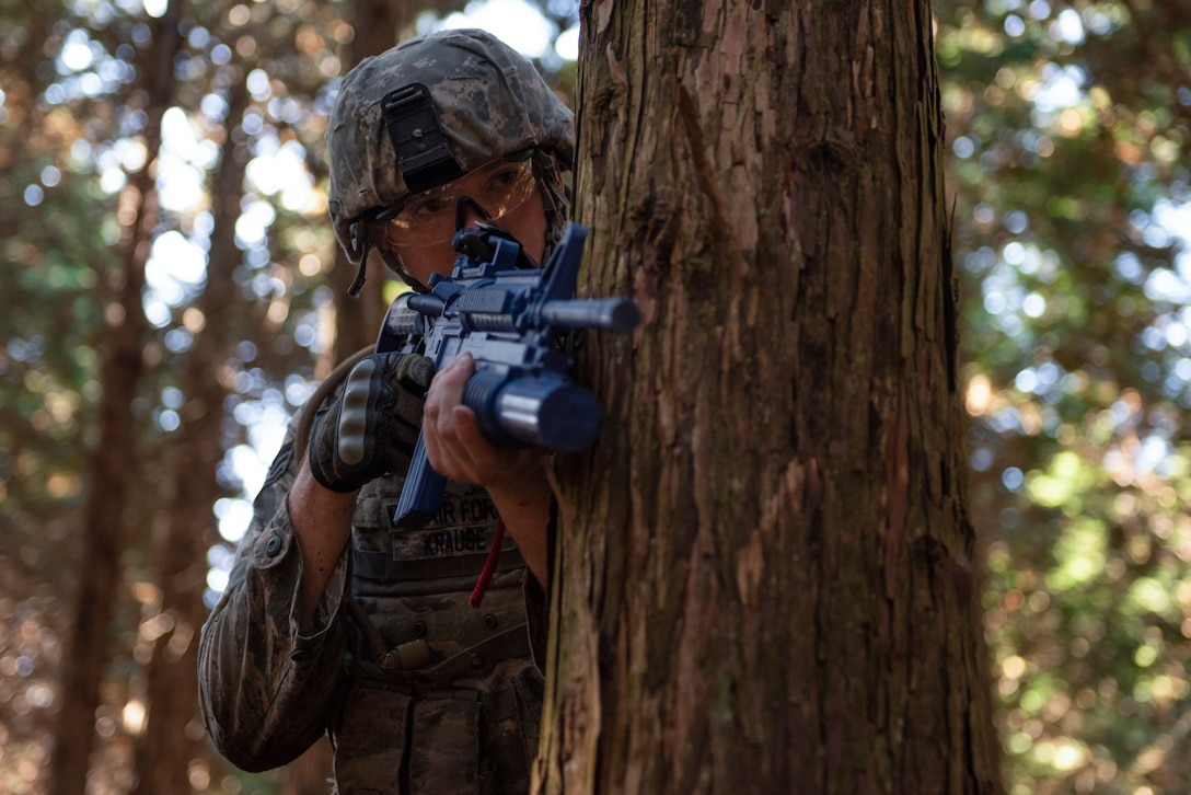 Senior Airman Mitchell Krause, 374th Security Forces Squadron patrolman, takes cover behind a tree during a field training exercise at Camp Fuji, Japan, Nov. 8, 2018.