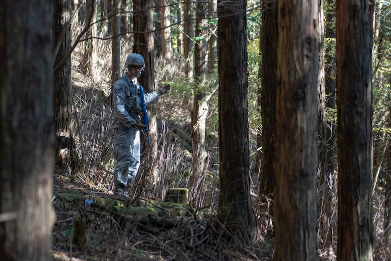 U.S. Air Force Tech. Sgt. Justin Hamilton, 374th Security Forces Squadron flight chief, motions to his team to follow during a field training exercise at Camp Fuji, Japan, Nov. 8, 2018.