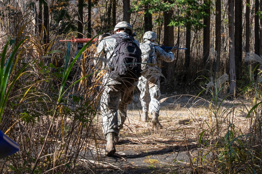 A pair of Airmen from the 374th Security Forces Squadron each cover a side as they pass through an open crossing during a field training exercise at Camp Fuji, Japan, Nov. 8, 2018.