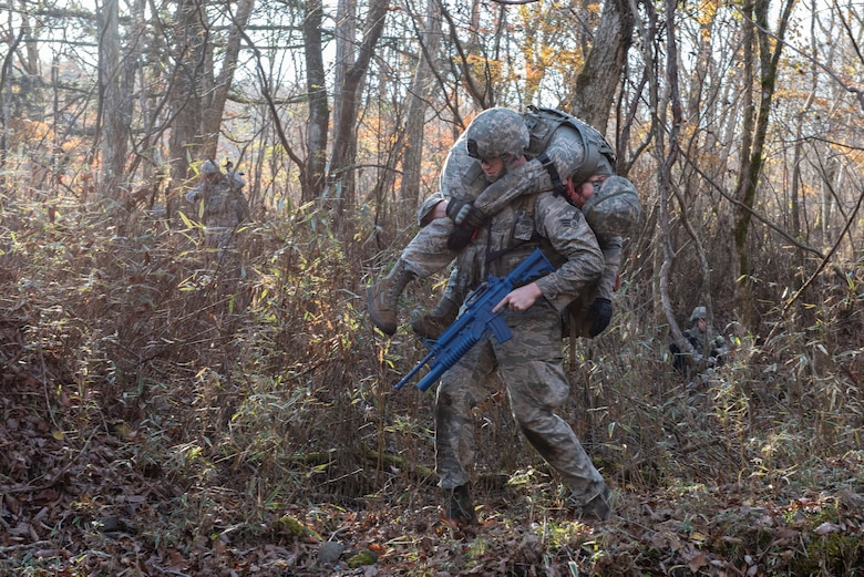 An Airman with the 374th Security Forces Squadron carries his fellow teammate with a simulated injury out of a danger area during a field training exercise at Camp Fuji, Japan, Nov. 8, 2018.