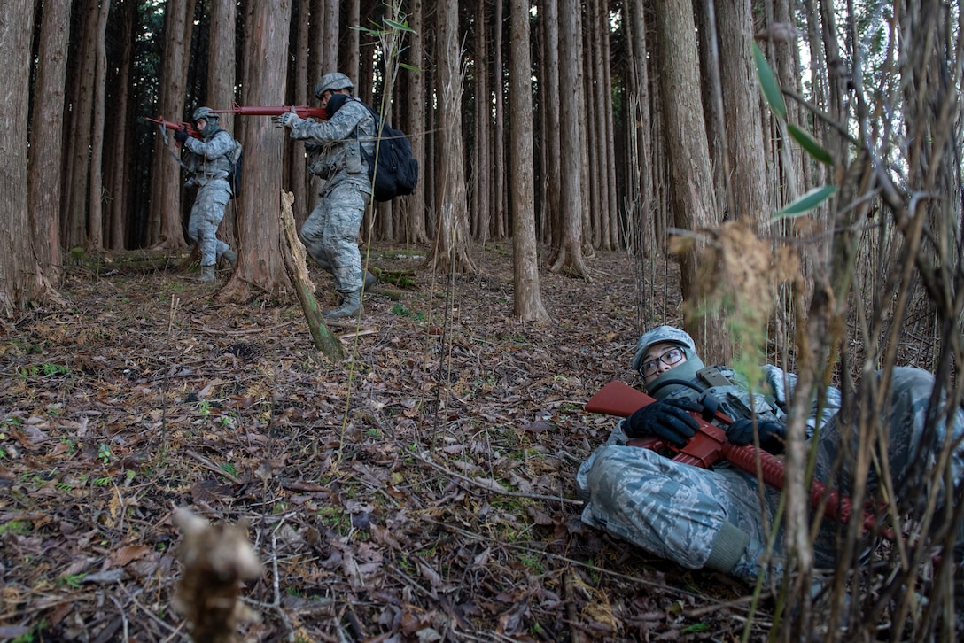 Airmen with the 374th Security Forces Squadron, top left, complete a sweep as a simulated enemy lays defeated on the right during a field training exercise at Camp Fuji, Japan, Nov. 8, 2018.