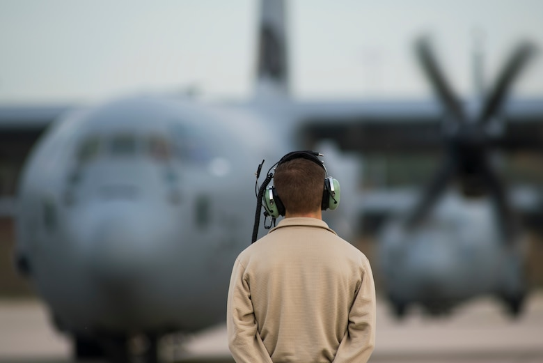 An 86th Aircraft Maintenance Squadron crew chief stands ready as a C-130J Super Hercules aircraft begins start up procedures on Ramstein Air Base, Germany, Nov. 6, 2018. Crew chiefs are responsible for the aircraft on the ground while aircrew responsible for the aircraft during missions. (U.S. Air Force photo by Senior Airman Devin M. Rumbaugh)