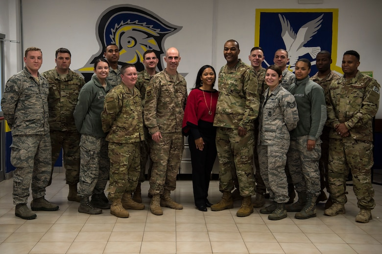 U.S. Air Force Col. Jason Bailey, 52nd Fighter Wing commander, center left, Chief Master Sgt. Alvin Dyer, 52nd FW command chief, center right, and his wife, Tanquer Dyer, center, pose for a photo with 704th Munitions Support Squadron Airmen at Ghedi Air Base, Italy, Nov. 15, 2018. Spangdahlem Air Base leadership visited the 704th MUNSS to support Airmen and learn base functions. Mrs. Dyer met and connected with spouses to encourage a family atmosphere between geographically separated units. (U.S. Air Force photo by Airman 1st Class Valerie Seelye)