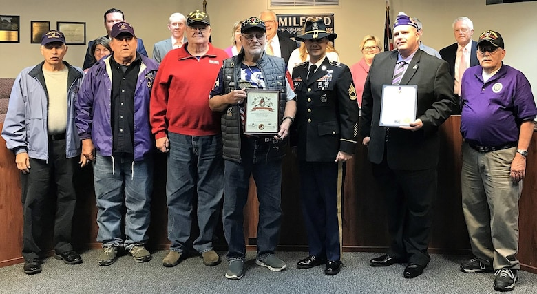 Twelve veterans and a Soldier in uniform at induction ceremony.