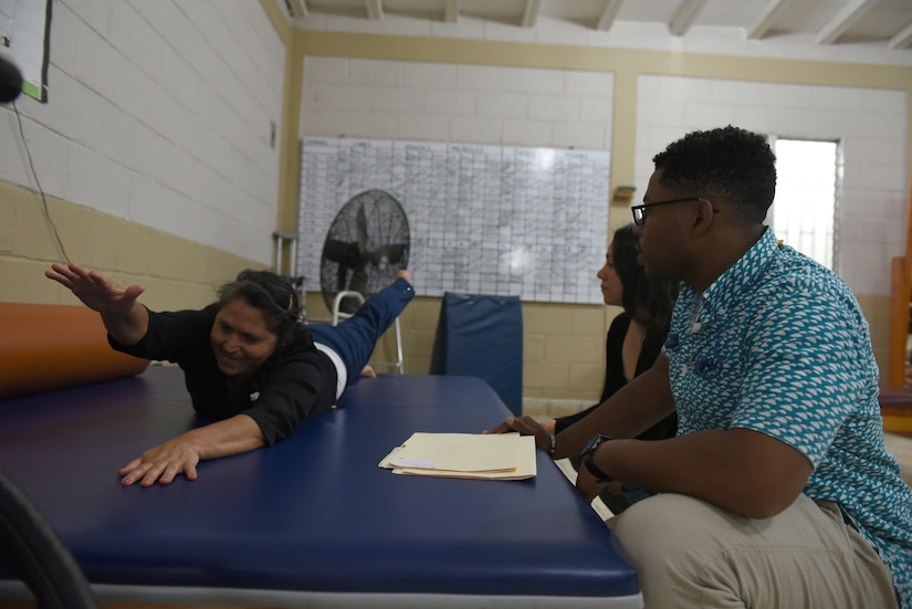 U.S. Army Spc. Devyn Leslie, Medical Element physical therapy technician helps guide his patient through exercises at a clinic in Comayagua, Nov. 8, 2018.