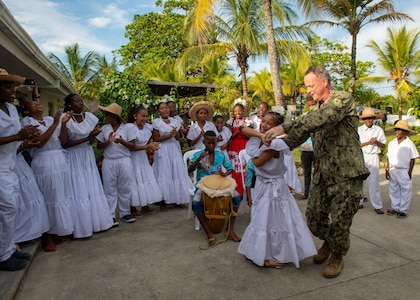 U.S. Navy Capt. Kevin Buckley, commanding officer, Medical Treatment Facility, of the hospital ship USNS Comfort (T-AH 20), dances with a member of a performance troupe following the opening ceremony at a land-based medical site.