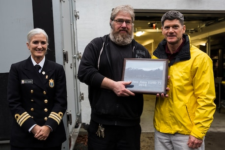 U.S. Navy Lt. Cmdr. Harold Woodruff, chaplain with the 24th Marine Expeditionary Unit, right, presents the Veterans Moter Veterans Home with a plaque of appreciation at the Veterans home in Oslo, Norway Nov. 15, 2018. Marines and Sailors with the 24th MEU and amphibious assault ship USS Iwo Jima (LHD 7) assisted in general maintenance, constructed a toy shelf and built relationships with Norwegian veterans. (U.S. Marine Corps photo by Cpl. Margaret Gale)