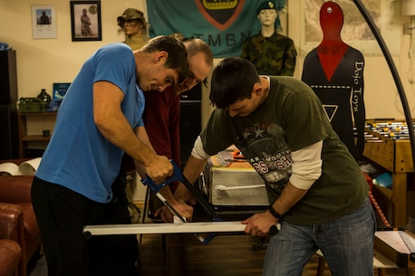Marines and Sailors, assigned to the 24th Marine Expeditionary Unit, build a toy-shelf in the Veterans Moter Veterans Home in Oslo, Norway Nov. 15, 2018. The service members, with the 24th Marine Expeditionary Unit and amphibious assault ship USS Iwo Jima (LHD 7), assisted in general maintenance, constructed a toy shelf, and built relationships with Norwegian veterans. The service members volunteered their time during a port visit in Oslo to assist the needs of the local community. (U.S. Marine Corps photo by Cpl. Margaret Gale)