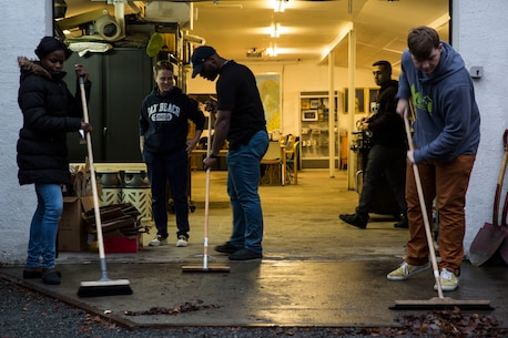 U.S. Navy Sailors sweep the garage of the Veterans Moter Veterans Home in Oslo, Norway Nov. 15, 2018. Marines and Sailors with the 24th Marine Expeditionary Unit and amphibious assault ship USS Iwo Jima (LHD 7) assisted in general maintenance, constructed a toy-shelf and built relationships with Norwegian veterans. The service members volunteered their time during a port visit in Oslo to assist the needs of the local community. (U.S. Marine Corps photo by Cpl. Margaret Gale)